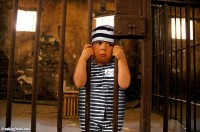 Little-Boy-in-Jail-Holding-Onto-Bars-29119